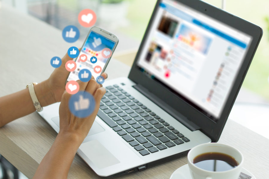Social Media für den Mittelstand, eine Frau sitzt mit Handy an einem Laptop